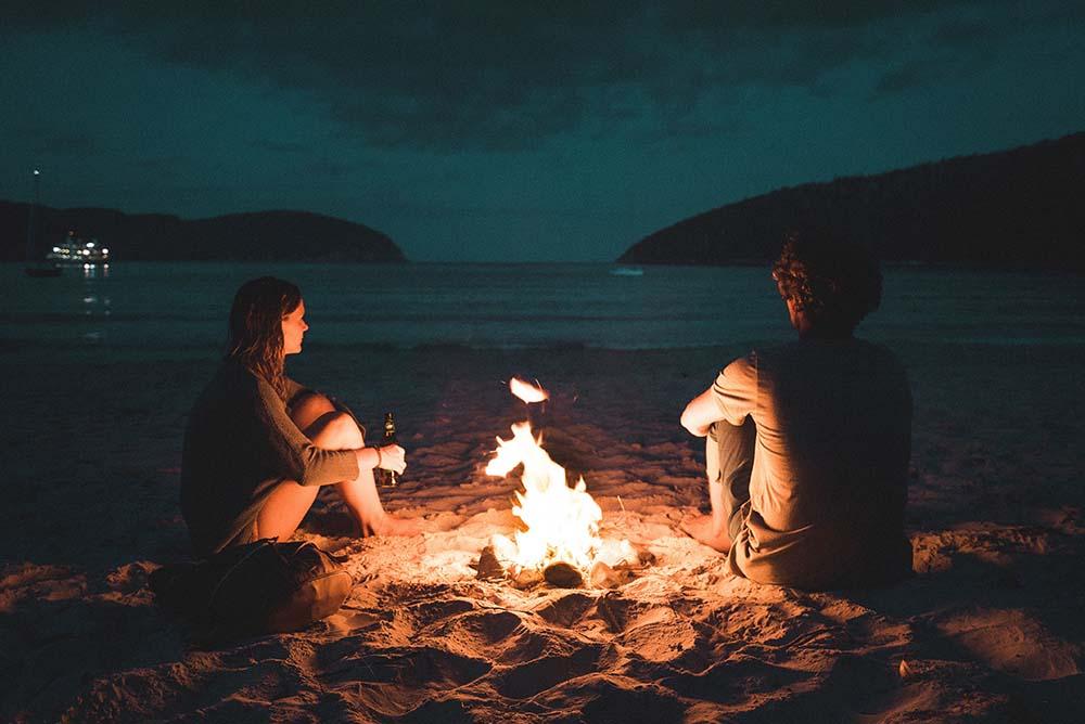 due ragazzi che parlano davanti ad un falò in spiaggia