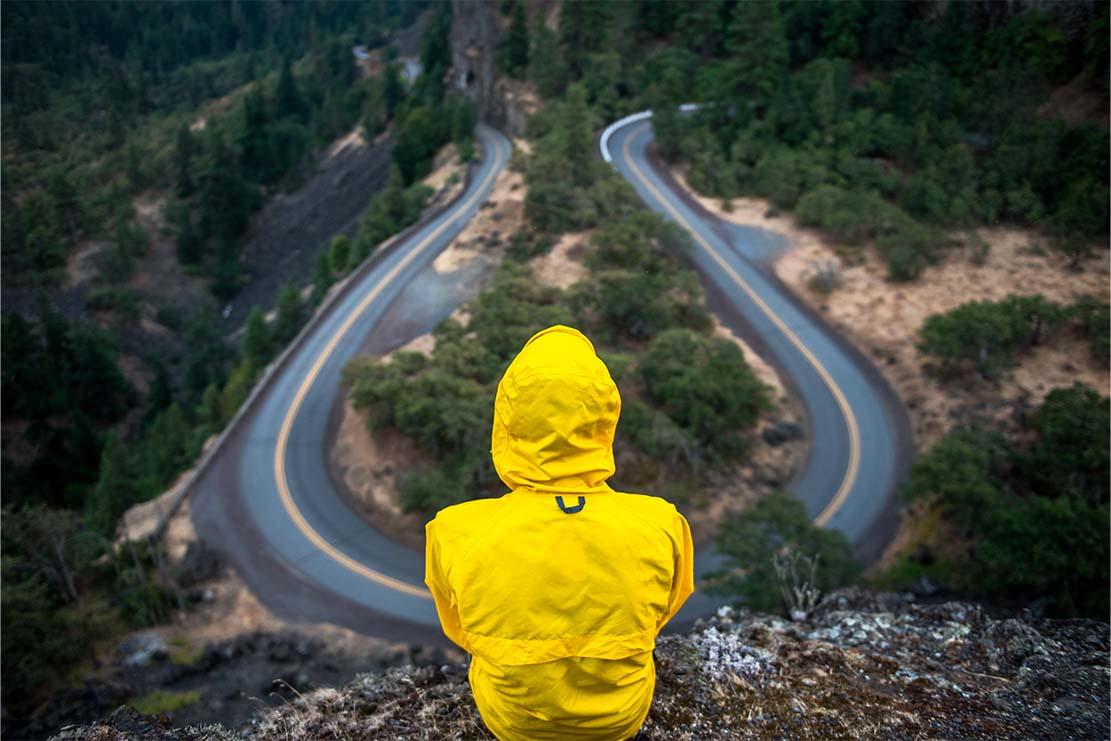 ragazzo su una montagna con kway giallo